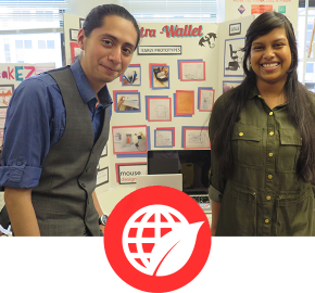 One male and one female student dressed business casual in front of their project board