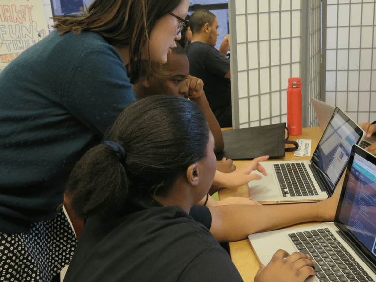 a female mentor assisting a male and female student on the chatbot project
