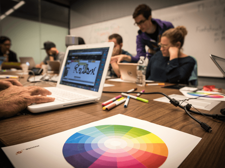 Image of color wheel and people working on intro to design course