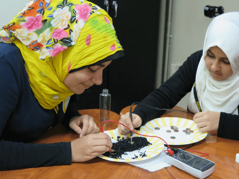 Two Female students building a battery with common material and measuring its power using multimeter