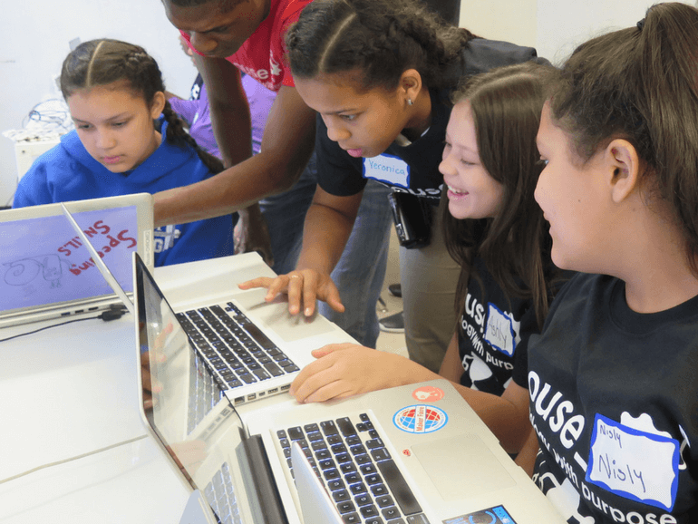 female students coding together in a group with a mentor helping another young lady on the side