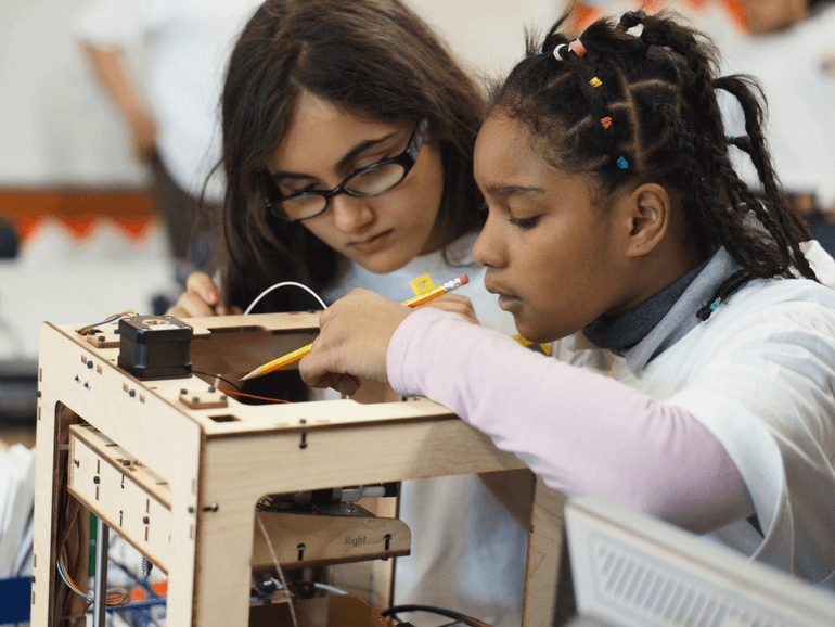 two girls working on understanding the parts of a MakerBot 3D printer