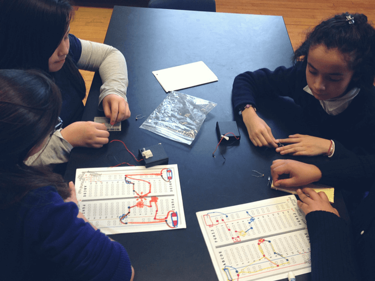 Group of girls building their circuits based on their design on paper