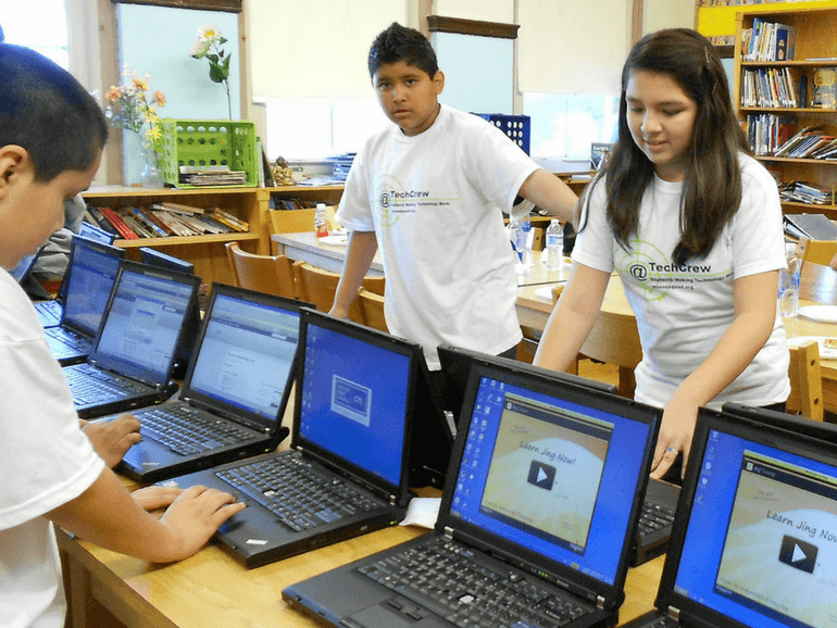 two boys and one girl managing school's laptops