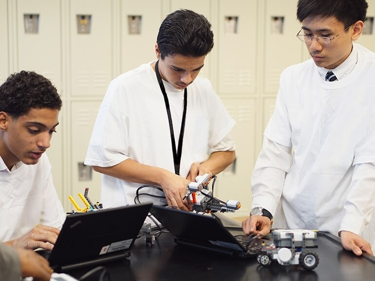 three students programming their lego robots using software on the laptop