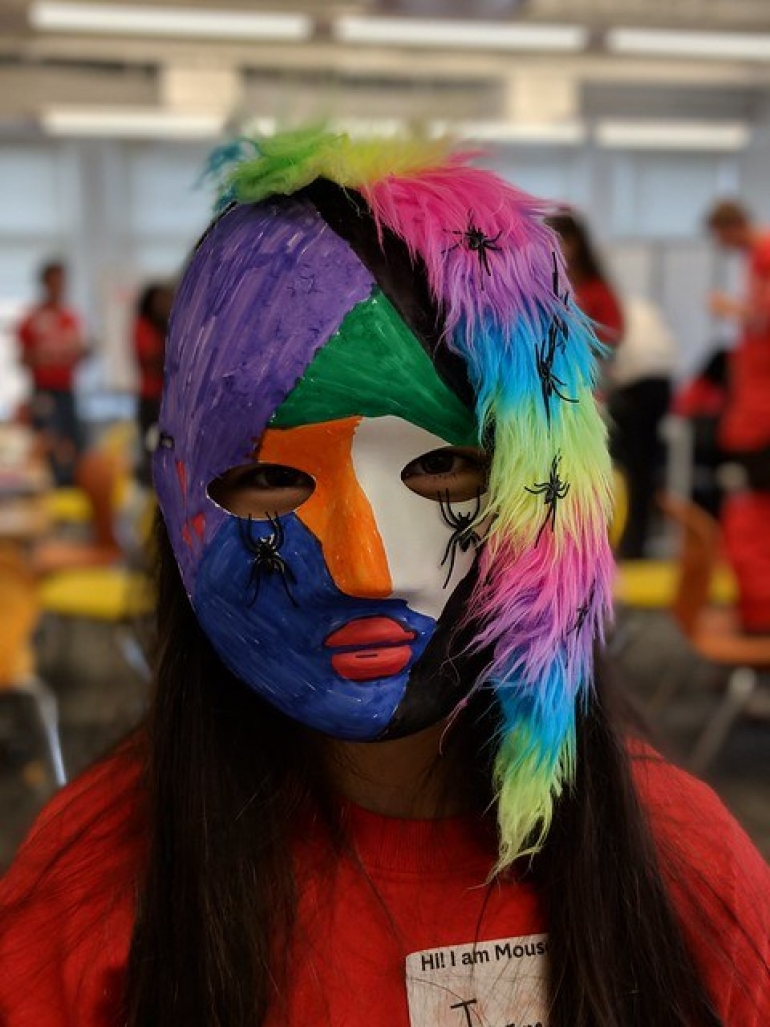 A young woman with a multicolor mask covering her face
