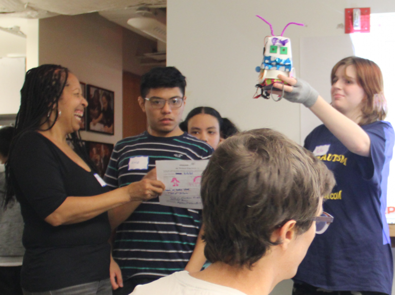 Darlene aiding her students in presenting their robot candidate on Robot Election at Mouse